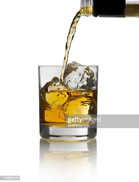 Gold liquor pouring into glass with ice on white background