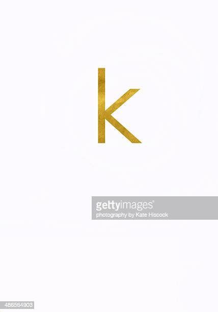 Gold lowercase letter k - paper cut