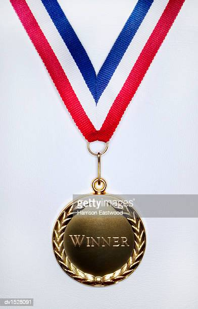 gold medal on a white background engraved with the single word winner - メダル ストックフォトと画像