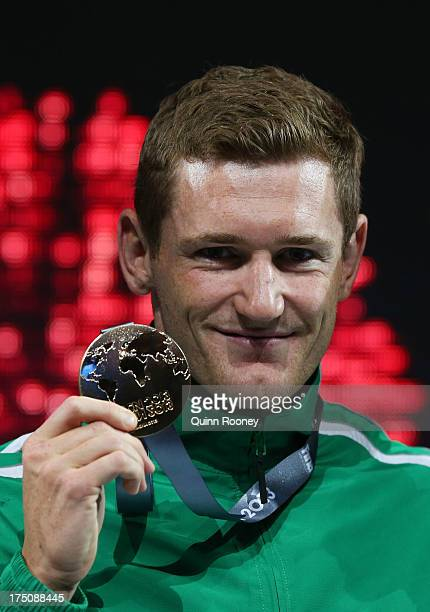 Gold medal winner Cameron Van Der Burgh of South Africa celebrates on the podium after the Swimming Men's 50m Breaststroke Final on day twelve of the...