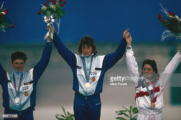 Gold medal winner Christa Rothenburger of East Germany stands on the podium flanked by [left] Kania of East Germany and [right] Bonnie Blair of the...