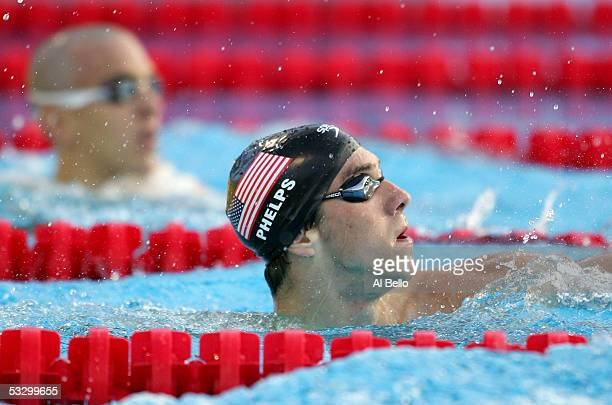 Gold medal winner Michael Phelps of the United States looks up at the scoreboard as he finishes ahead of silver medal winner Lazlo Cseh of Hungary...