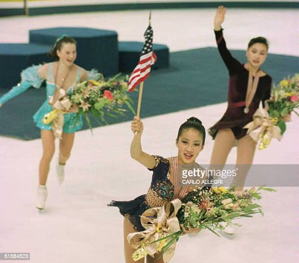 Gold medal winner Michelle Kwan skates from the medal podium with bronze medalist Irina Slutskaya of Russia and silver medalist Lu Chen of China...