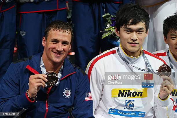 Gold medal winner Ryan Lochte of the USA and Bronze medal winner Yang Sun of China celebrate on the podium after the Men's Freestyle 4x200m Final on...