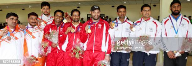 Gold medal winner team members of Services Silver Medal winners of Karnataka and Bronze medal winners of Uttar Pradesh showing their medals after...