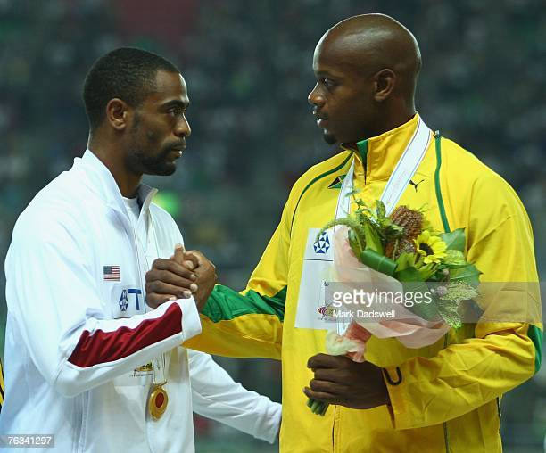 Gold Medal winner Tyson Gay of the United States of America shakes hands with Bronze Medal winner Asafa Powell of Jamaica as they receive their...