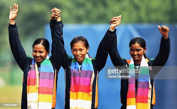 Gold medal winners Dola Banerjee, Bombayala Devi Laishram and Deepika Kumari of India celebrate during the medal ceremony for the Women's Team...