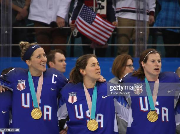 Gold medal winners Meghan Duggan Haley Skarupa and Kelly Pannek of the United States look on during the national anthem after defeating Canada in a...