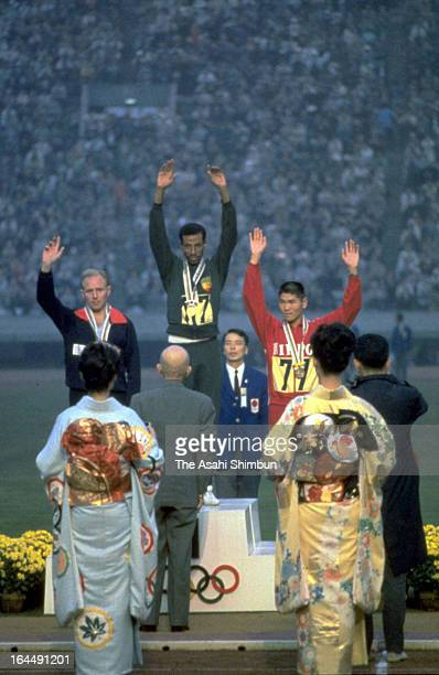 Gold Medalist Abebe Bikila of Ethiopia, Silver Medalist Basil Heatley of Great Britain and Bronze Medalist Kokichi Tsuburaya of Japan pose for...