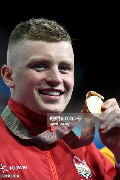 Gold medalist Adam Peaty of England poses during the medal ceremony for the Men's 100m Breaststroke Final on day three of the Gold Coast 2018...