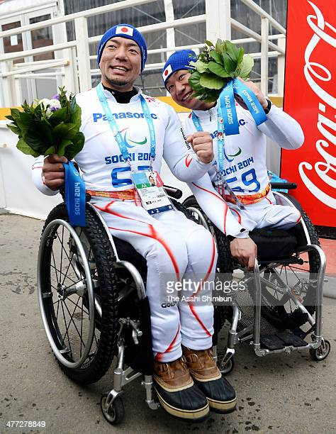 Gold medalist Akira Kano and bronze medalist Takeshi Suzuki of Japan celebrate after the flower ceremony following the Men's Downhill Sitting during...