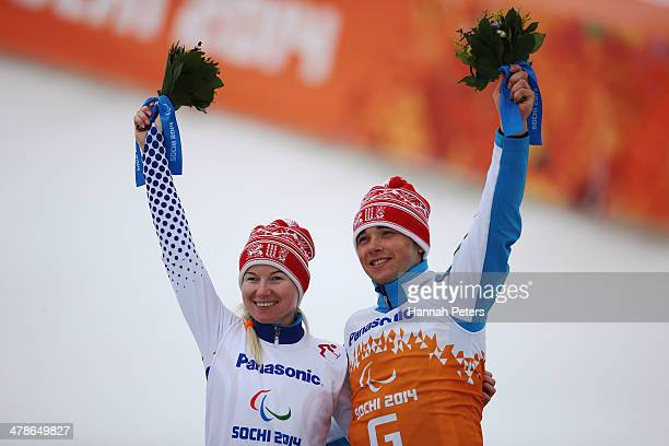 Gold medalist Aleksandra Frantceva of Russia and guide Pavel Zabotin celebrate during the flower ceremony for the Women's Super Combined Visually...