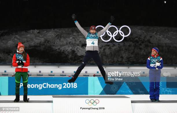 Gold medalist Anastasiya Kuzmina of Slovakia celebrates alongside silver medalist Darya Domracheva of Belarus and bronze medalist Tiril Eckhoff of...