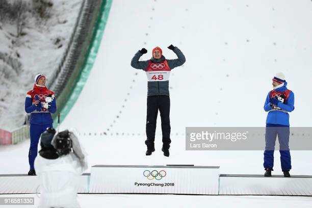 Gold medalist Andreas Wellinger of Germany celebrates on the podium alongside silver medalist Johann Andre Forfang of Norway and bronze medalist...