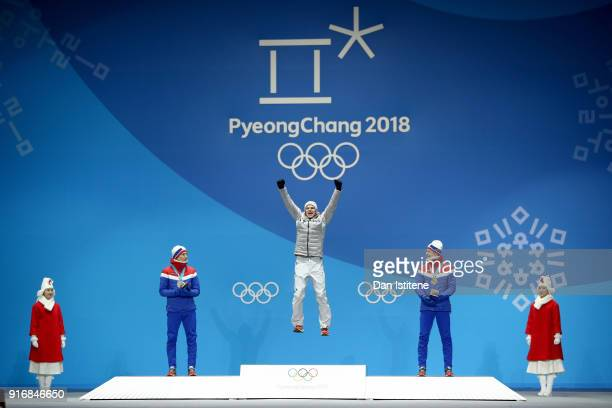 Gold medalist Andreas Wellinger of Germany celebrates on the podium with silver medalist Johann Andre Forfang of Norway and bronze medalist Robert...