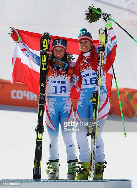 Gold medalist Anna Fenninger of Austria and bronze medalist Nicole Hosp of Austria celebrate on the podium during the flower ceremony for the Alpine...
