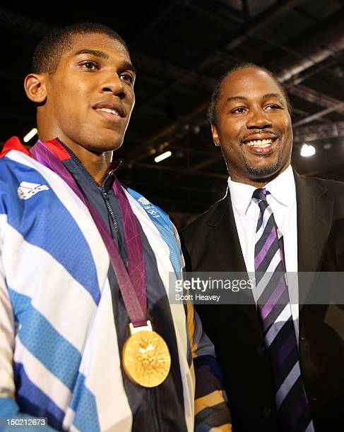 Gold medalist Anthony Joshua of Great Britain celebrates with former world heavweight boxing champion and fellow countryman Lennox Lewis after the...