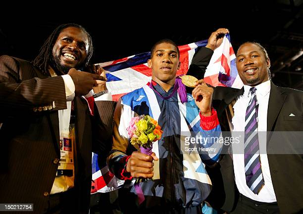 Gold medalist Anthony Joshua of Great Britain celebrates with former world heavweight boxing champion Lennox Lewis and British professional boxer and...