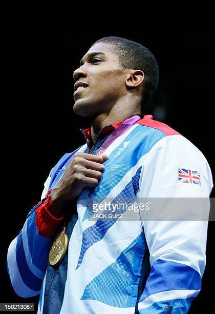 Gold medalist Anthony Joshua of Great Britain listens to the British national anthem during the awards ceremony for the SuperHeavyweight boxing...