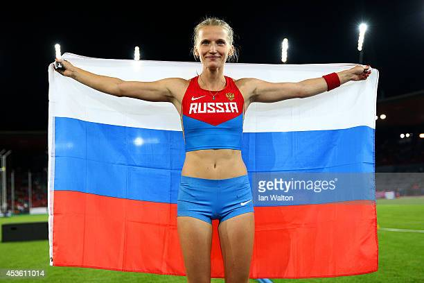 Gold medalist Anzhelika Sidorova of Russia poses with the Russian national flag as she celebrates after the Women's Pole Vault final during day three...
