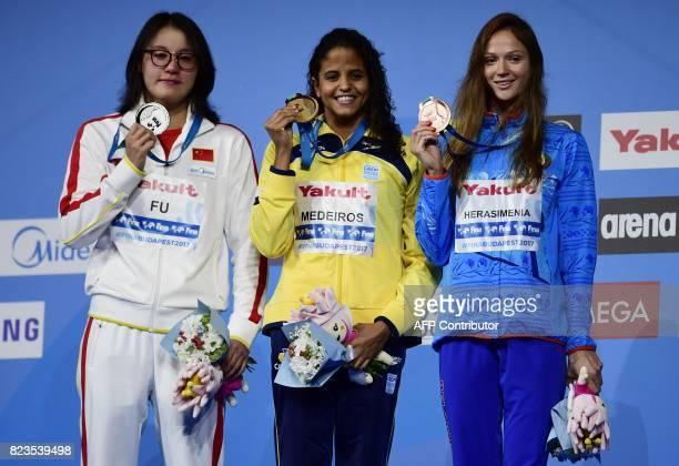 Gold medalist Brazil's Etiene Medeiros silver medalist China's Fu Yuanhui and bronze medalist Belarus' Aliaksandra Herasimenia celebrate on the...