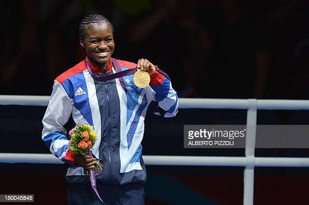 Gold medalist Britain's Nicola Adams celebrates on the podium of the the women's boxing Flyweight final of the 2012 London Olympic Games at the ExCel...