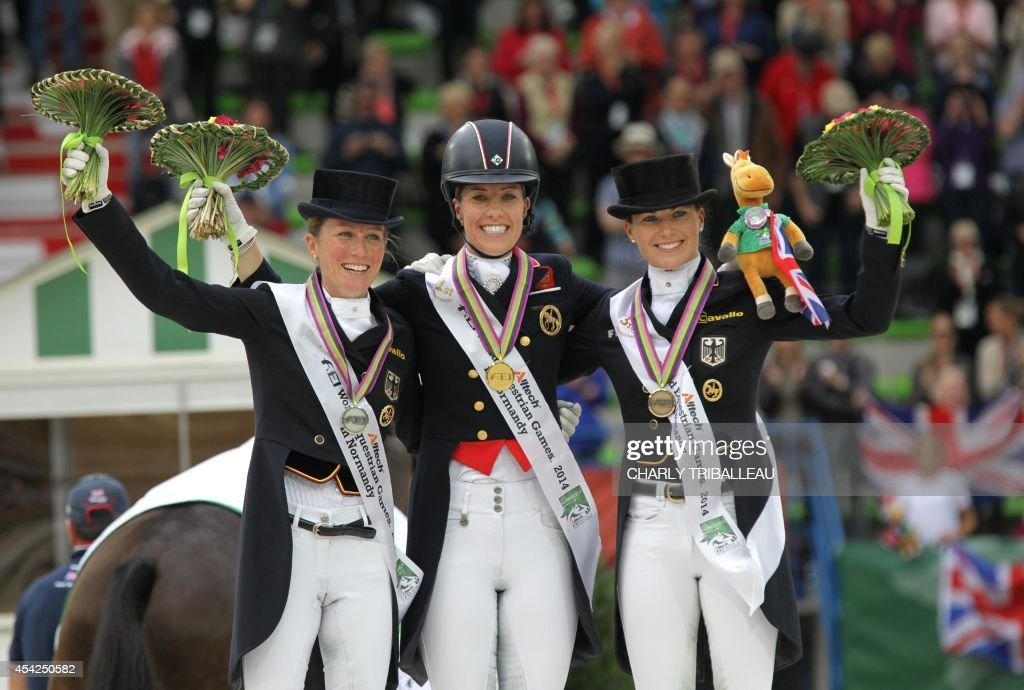 Gold medalist British Charlotte Dujardin (C), silver medalist German Helen Langehanenberg (L) and bronze medalist German Kristina Sprehe pose on the podium during the medals ceremony of the Individual Dressage Grand Prix of the 2014 FEI World Equestrian Games at D'Ornano Stadium in the northwestern French city of Caen on August 27, 2014.