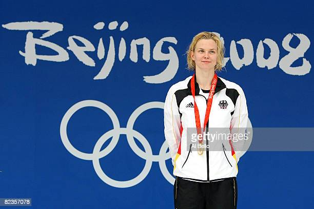 Gold medalist Britta Steffen of Germany stands on the podium during the medal ceremony for the Women's 100m Freestyle Final held at the National...