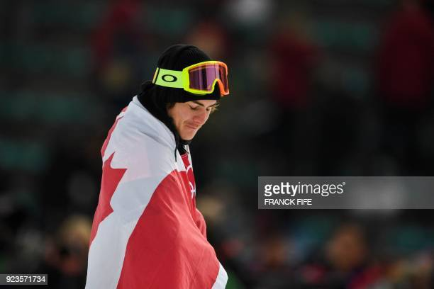 TOPSHOT Gold medalist Canada's Sebastien Toutant is draped in the Canadian national flag following the final of the men's snowboard big air event at...