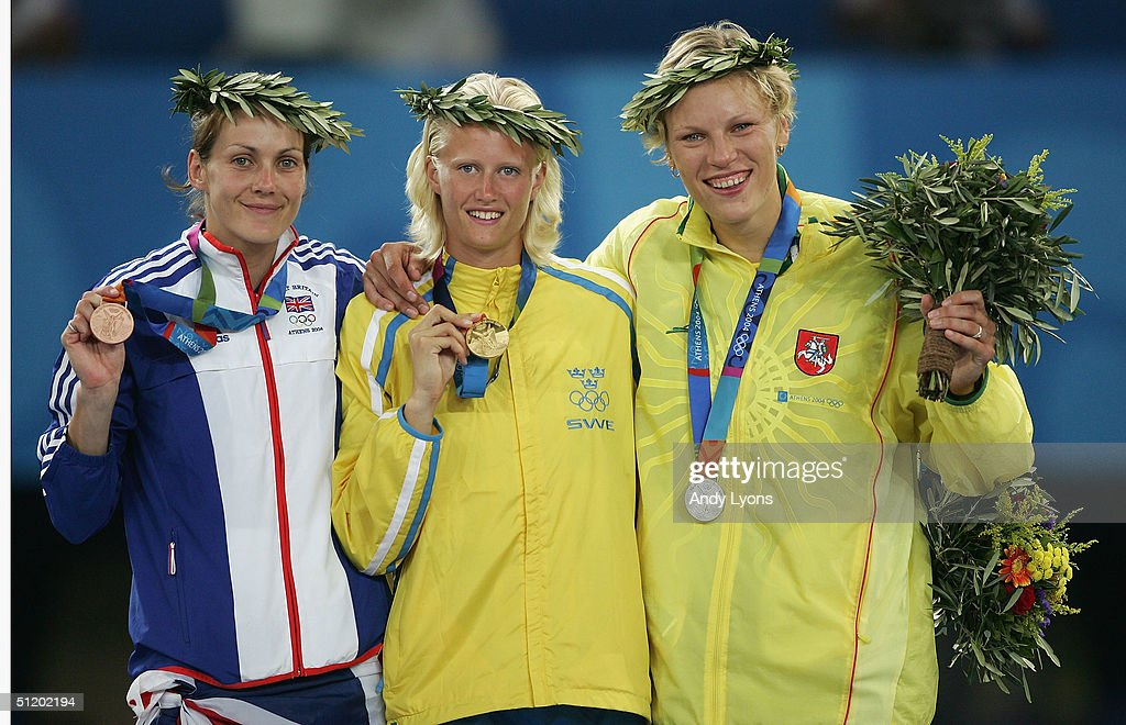 Gold medalist Carolina Kluft of Sweden, silver medalist Austra Skujyte of Lithuania (R) and bronze medalist Kelly Sotherton of Great Britain (L) celebrate on the podium during the medal ceremony of the women's heptathlon event on August 21, 2004 during the Athens 2004 Summer Olympic Games at the Olympic Stadium in the Sports Complex in Athens, Greece.