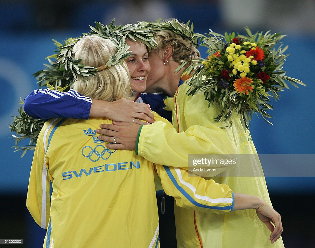 Gold medalist Carolina Kluft of Sweden, silver medalist Austra Skujyte of Lithuania (R) and bronze medalist Kelly Sotherton of Great Britain (C) celebrate on the podium during the medal ceremony of the women's heptathlon event on August 21, 2004 during the Athens 2004 Summer Olympic Games at the Olympic Stadium in the Sports Complex in Athens, Greece.