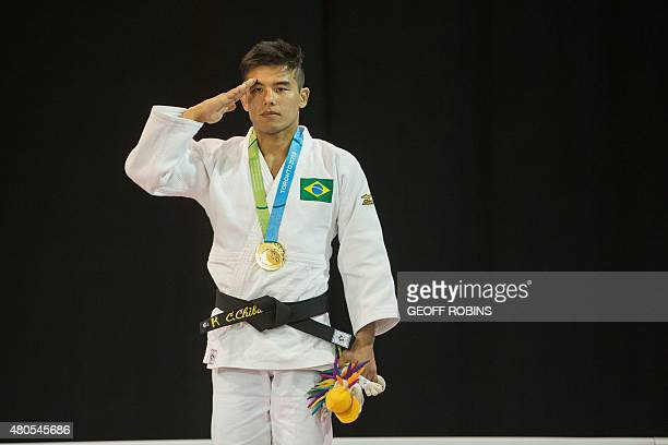 Gold medalist Charles Chibana salutes as the Brazilian national anthem is played during the medal ceremony for the men's judo 66kg class at the 2015...