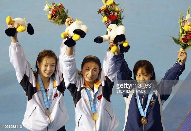 Gold medalist China's Guo Jingjing celebrates with the other medal winners teammate Wu Minxia with the silver and Japan's Ryoko Nishi with the bronze...