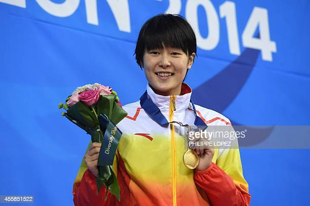 Gold medalist China's Zhang Yuhan poses with her medal on the podium during the victory ceremony for the women's 400m freestyle swimming event during...
