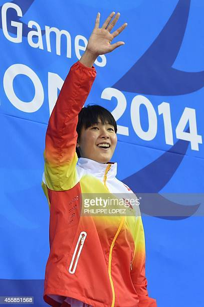 Gold medalist China's Zhang Yuhan waves on the podium during the victory ceremony for the women's 400m freestyle swimming event during the 17th Asian...