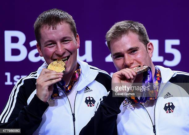 Gold medalist Christian Reitz of Germany and bronze medalist Oliver Geis of Germany pose with the medals won during the Men's Shooting 25m Rapid Fire...