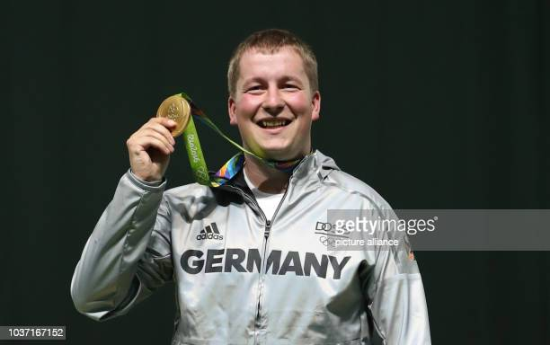 Gold medalist Christian Reitz of Germany celebrates during the medal ceremony of the 25m Rapid Fire Pistol Men's final in the Shooting events during...