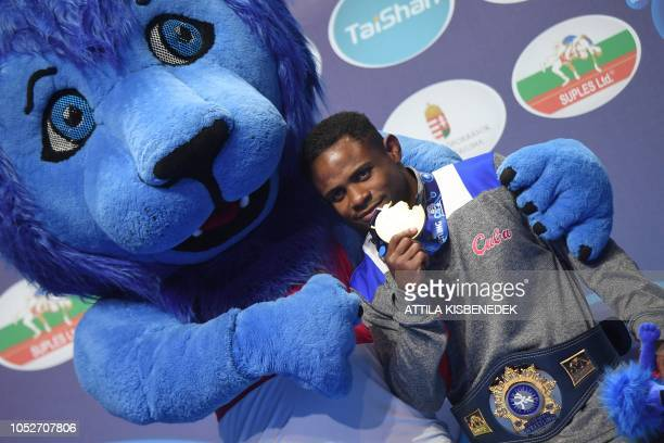 TOPSHOT Gold medalist Cuba's Yowlys Bonne Rodriguez celebrates on the podium after the men's freestyle wrestling 61kg category at the World Wrestling...