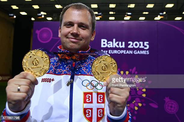 Gold medalist Damir Mikec of Serbia poses with the medals won during the Men's Pistol Shooting 50m final and 10 m final on day eight of the Baku 2015...