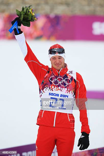 Gold medalist Dario Cologna of Switzerland celebrates during the flower ceremony for the Men's Skiathlon 15 km Classic + 15 km Free during day two of...