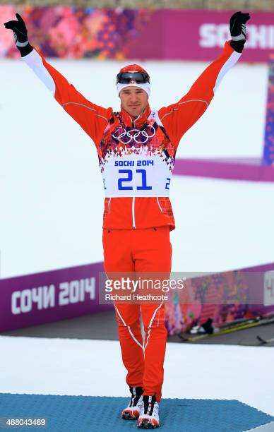 Gold medalist Dario Cologna of Switzerland stands on the podium during the flower ceremony for the Men's Skiathlon 15 km Classic + 15 km Free during...