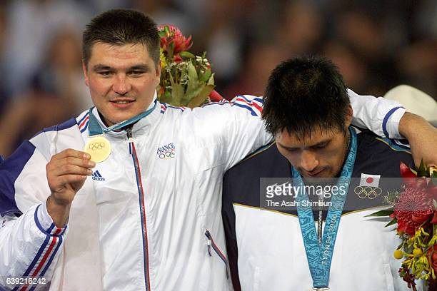 Gold medalist David Douillet of France and silver medalist Shinichi Shinohara of Japan are seen on the podium at the medal ceremony for the Men's...