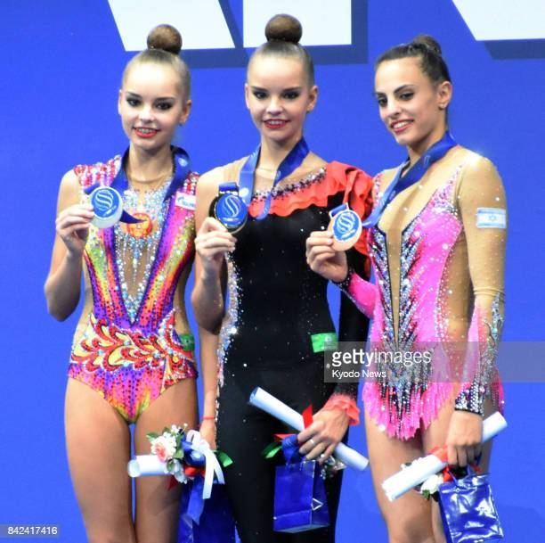 Gold medalist Dina Averina of Russia her twin sister and silver medalist Arina Averina and bronze medalist Linoy Ashram of Israel pose for photos...