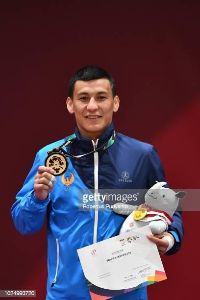 Gold medalist Diyorbek Urozboev of Uzbekistan celebrates on the podium during Men's Judo -60kg victory ceremony at JCC Plenary Hall on day eleven of...