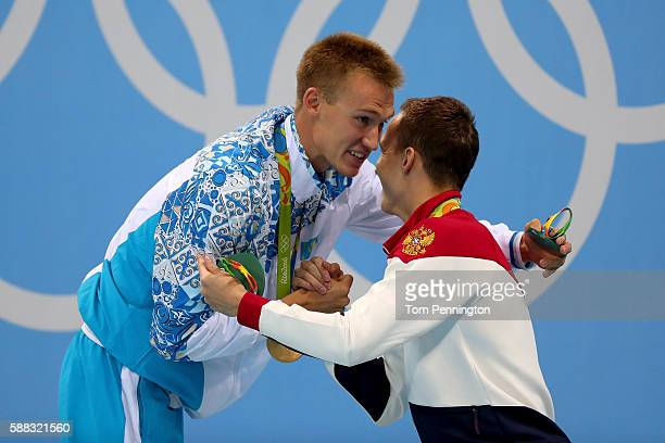 Gold medalist Dmitriy Balandin of Kazakhstan and bronze medalist Anton Chupkov of Russia congratulate each other on the podium during the medal...
