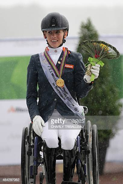 Gold medalist Dutch Rixt van der Horst celebrates on the podium during the medal ceremony of the Individual Grade II ParaDressage of the 2014 FEI...