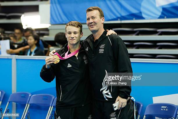 Gold medalist Dylan Schmidt of New Zealand with coach celebrate during the medal ceremony after the Men's Trampoline Gymnastic Final of Nanjing 2014...