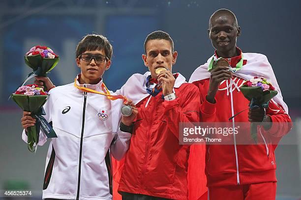 Gold medalist Elhassan Elabbassi of Bahrain Silver medalist Suguru Osako and Bronze medalist Isaac Korir of Bahrain pose atop the podium following...