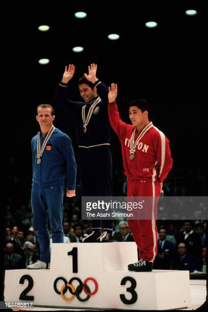 Gold Medalist Enyu Valtchev of Bulgaria Silver Medalist KlausJurgen Rost of Germany and Bronze Medalist Iwao Horiuchi of Japan waves on the podium at...