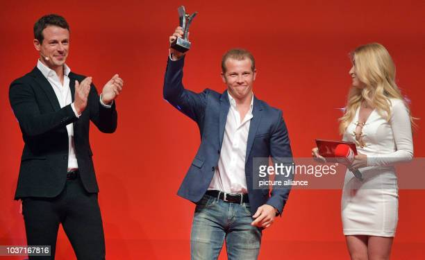 Gold medalist Fabian Hambuechen celebrates his award with presenters Andrea Kaiser and Alexander Bommes at the Sport BildAward ceremony in Hamburg...